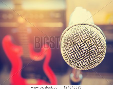 Microphone in in a recording studio or concert hall with red electric guitar in out of focus background. : Vintage style and filtered process.
