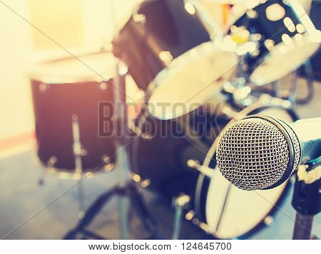 Microphone in in a recording studio or concert hall with drum in out of focus background. Vintage style and filtered process.