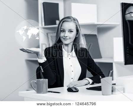 Young business woman present digital map in office. Elements of this image furnished by NASA