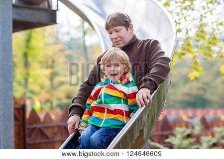 Young dad and little son having fun on playground slide. Kid boy and man sliding together and laughing. Happy family on warm sunny day.