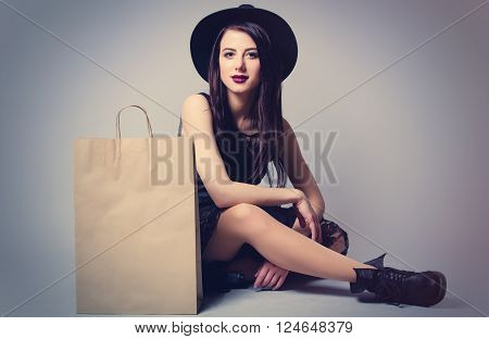 portrait of the beautiful young woman with shopping bag sitting on the grey background