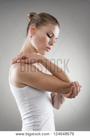 Portrait of young woman having joint pain and massaging her elbow over grey background.