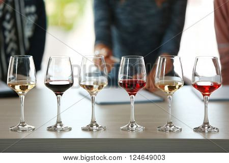 Many glasses of different wine in a row on a table. Tasting wine concept