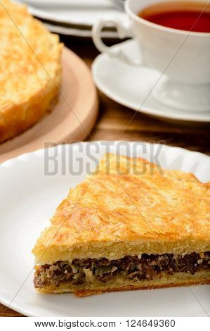Piece of pie with minced meat on wooden table.