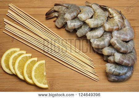 Many Raw  Shrimps On Skewer With Lemon On Wooden Background
