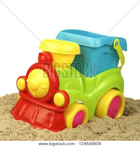 Close-up Of Toy Train With Kinetic Sand Heap Isolated On White Background. Childrens Creativity Or Beach Game Concept.