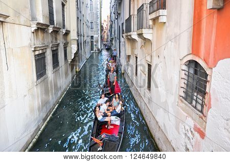 VENICE-JUNE 21: Gondoliers run the gondolas tourists enjoy sightseeing on the Venetian canal on June 21 2010 in Venice Italy.