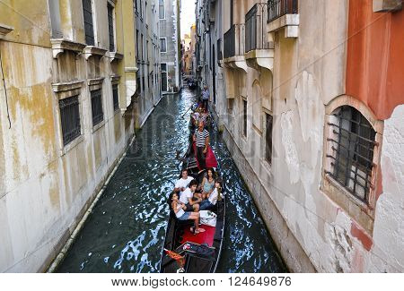 VENICE-JUNE 15: Gondolier runs the gondola with group of tourists on the Venetian canal on June 15 2012 in Venice Italy.