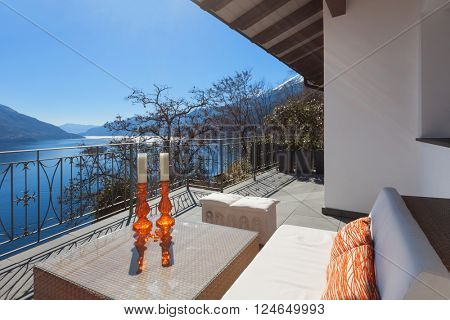 Terrace lounge with comfortable divan and lake view in a luxury house