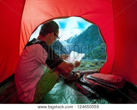 camping man reading traveling guide book in camp tent against beautiful scenic of glacier mountain