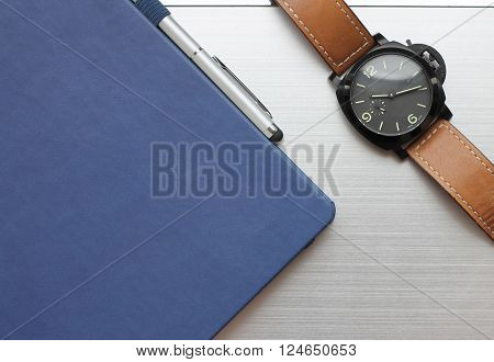Notebook pen with diary and watch lying on a laptop.