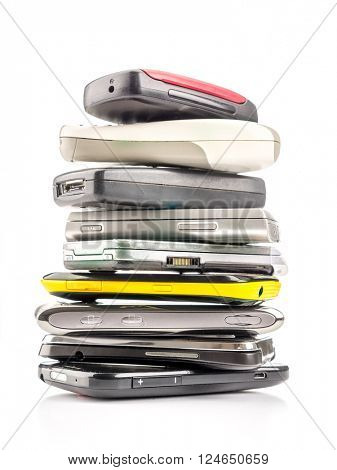 Pile of old and used mobile phones on white background