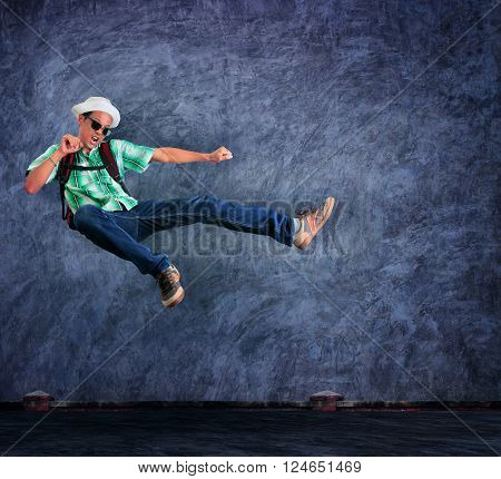 traveling man jumping mid air with exciting emotion against cement wall