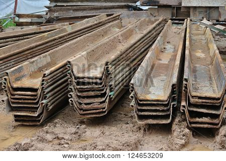 MALACCA, MALAYSIA -SEPTEMBER 25, 2015: Stack of retaining wall steel sheet pile cofferdam lay on ground at the construction site in Malaysia