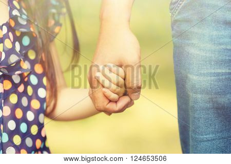 Father's hand lead his child daughter outdoors, trust family concept