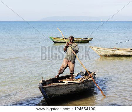 SAINTARD, HAITI -  An unidentified Haitian fisherman standing on his boat as he pushes away from the shore with a long pole near Saintard, Haiti on March 2, 2016.
