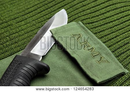Khaki Or Green Color Woven Warm Military Fabric Textile Or Sweater With Army Sign and Silver Torch Laying On It Closeup Detail Army Concept