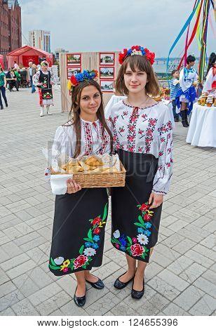 Dnepropetrovsk Ukraine - September 14 2013: Girls in Ukrainian national costumes sold buns for charitable purposes