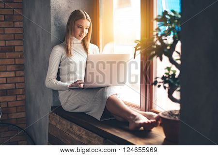 Surfing net at home. Beautiful young woman using her laptop while sitting at windowsill at home