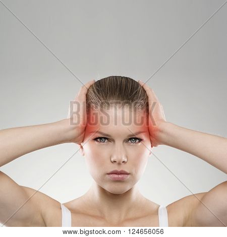 Closeup portrait of exhausted woman with vertigo or headache problem. Young attractive Caucasian female suffering from chronic migraine.