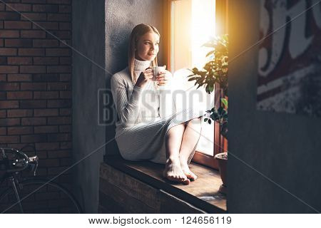 Making plans for new day. Beautiful young woman holding coffee cup and looking through window while sitting at windowsill at home