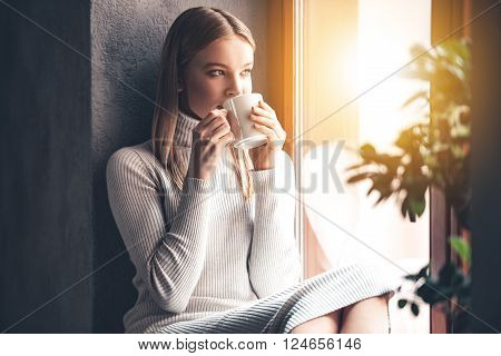 Enjoying her fresh coffee. Beautiful young woman drinking coffee and looking through window while sitting at windowsill at home