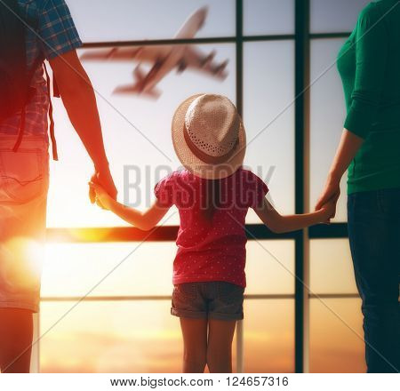 Happy family with child at the airport. Parents and child girl look out the window at the airplane.
