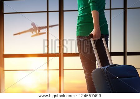 Young beautiful woman looks at a plane at the airport.