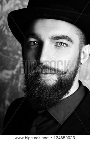 Gentleman with beard and mustache wearing elegant suit and top hat. Old style fashion.