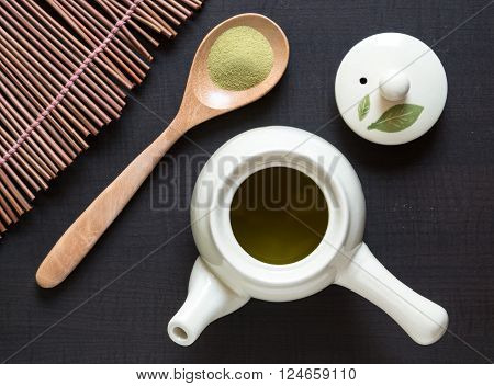 Top view of green tea matcha with wooden a spoon on bamboo wooden.