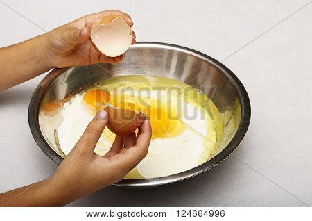 Child's Hand Breaking Eggs