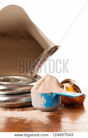 Whey Protein Powder In Measuring Scoop, Meter Tape And Dumbbell On Wooden Background.