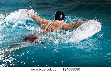 Young healthy man with muscular body swims in swimming pool