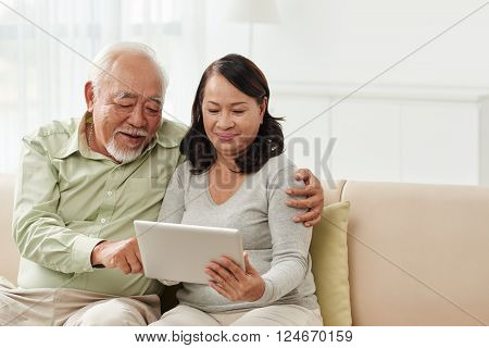 Senior Vietnamese couple with digital tablet sitting on sofa at home