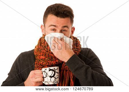 Man With Flu And Fever Wrapped In Scarf Holding Cup Of Healing Tea And Handkerchief.