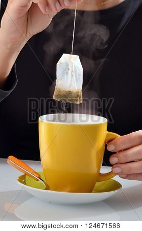 Woman soaking tea bag on yellow cup, preparing hot tea.Dipping teabag on cup.