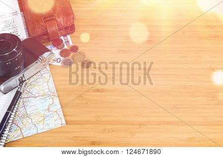 getting ready for travel, money, map and photo camera on wooden table with copy space and sun flare