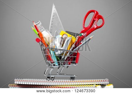 Shopping cart full of school tools on grey background