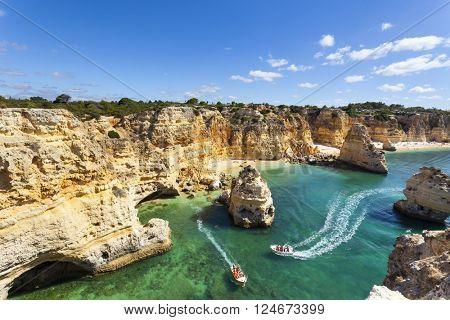 Boat with tourists visiting the caves near the beach ( praia da Marinha ), Algarve