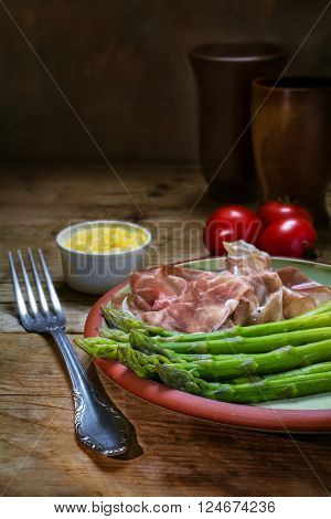green asparagus with gammon and hollandaise sauce on an earthenware plate on a rustic wooden table dark background copy space vertical selected focus narrow depth of field