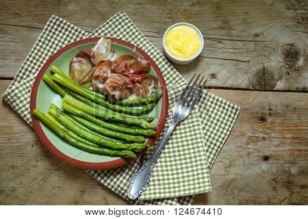 green asparagus with gammon and dip on an earthenware plate on a napkin, rustic wooden background, view from above, copy space