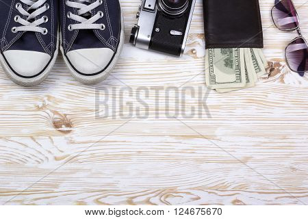 still life with sneakers, camera, sunglasses and wallet with dollars