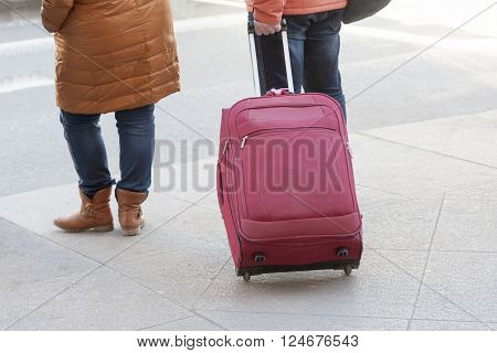 legs of the person rolling a tourist bag on wheels in summer day