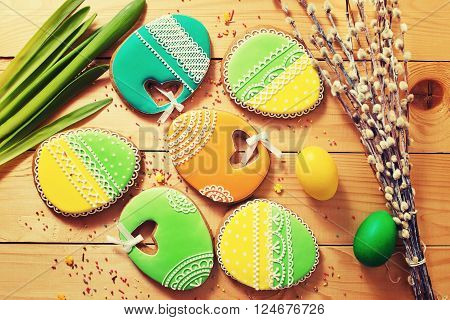 Easter homemade gingerbread cookie and yellow end green eggs over wooden table. Colorful toned image top view