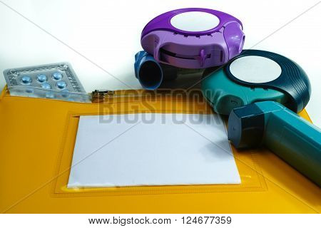 Asthma relief concept salbutamol inhaler another medication and yellow medical plastic bag copy space