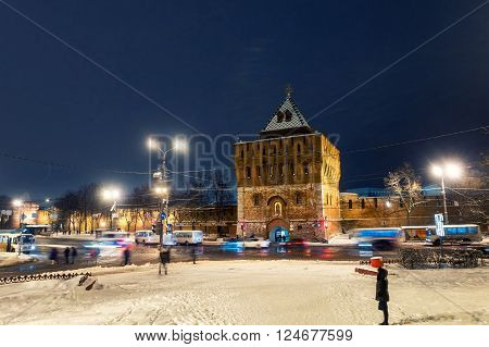 Illuminated Kremlin wall and main gate in Nizhny Novgorod Russia in winter with white snow everywhere at night. Car traffic and dark sky