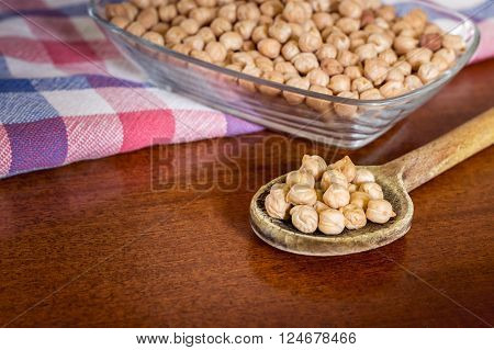 Uncooked chickpeas in old wooden spoon with glass bowl of chickpeas and kitchen rag in background. Copy space