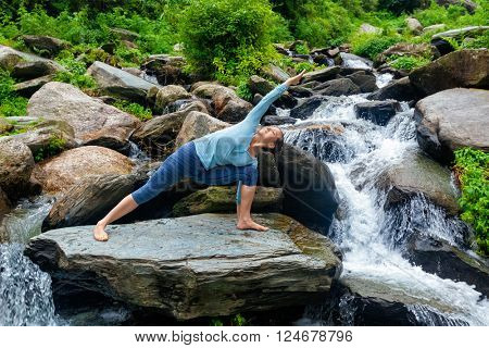 Sporty fit woman practices yoga asana Utthita Parsvakonasana -  extended side angle pose outdoors at water
