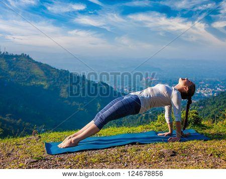 Woman doing Hatha yoga asana Purvottanasana plank pose  outdoors in mountains