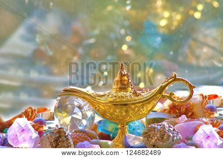 Image of a golden lamp and gemstones